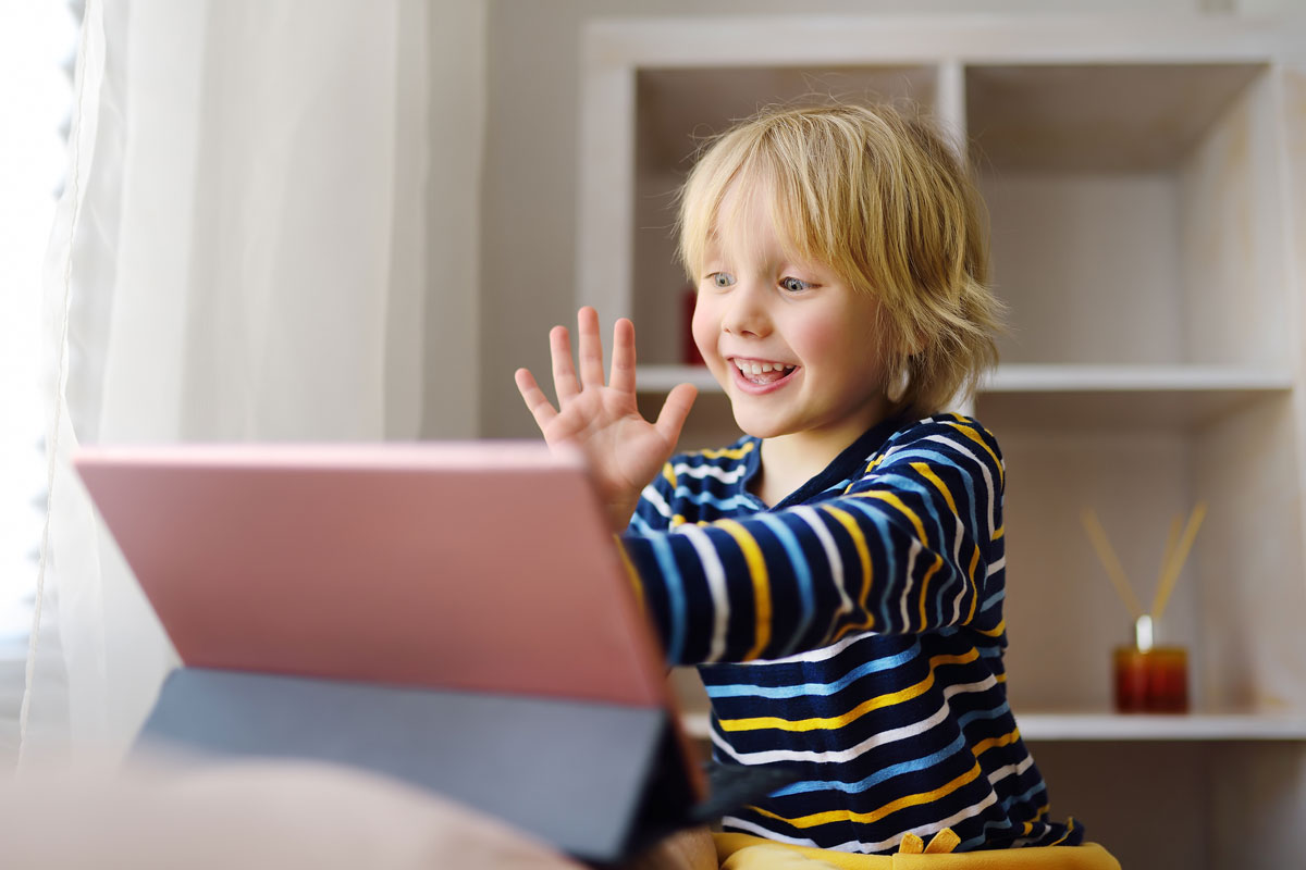 a small child waving to someone over video chat on a tablet