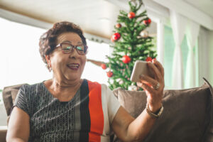 a senior woman using FaceTime on her cell phone with a Christmas tree in the background