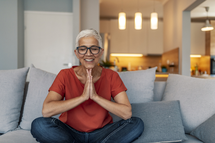 a senior woman practicing yoga on her couch