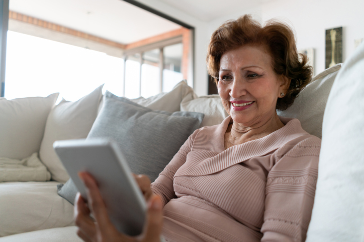 a senior woman sitting on her couch looking at a tablet