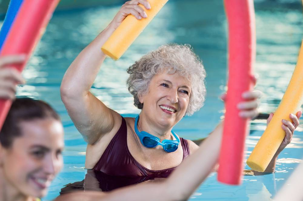 Senior woman participating in water aerobics with pool noodle