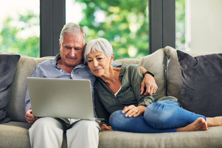 senior couple uses laptop on couch at home