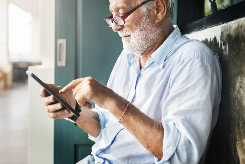 senior man typing on his smart phone