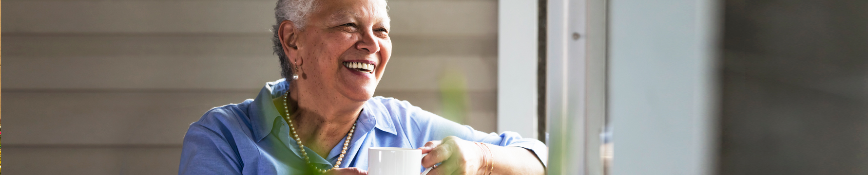 A senior woman smiling while drinking coffee outside on the deck