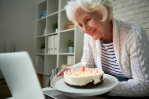 a senior woman celebrating a loved ones birthday with cake over a video call