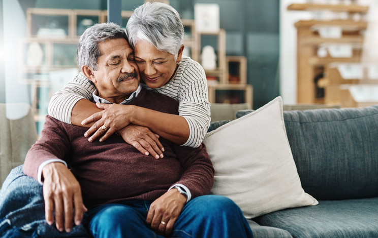 an elderly couple hugging one another while on their couch