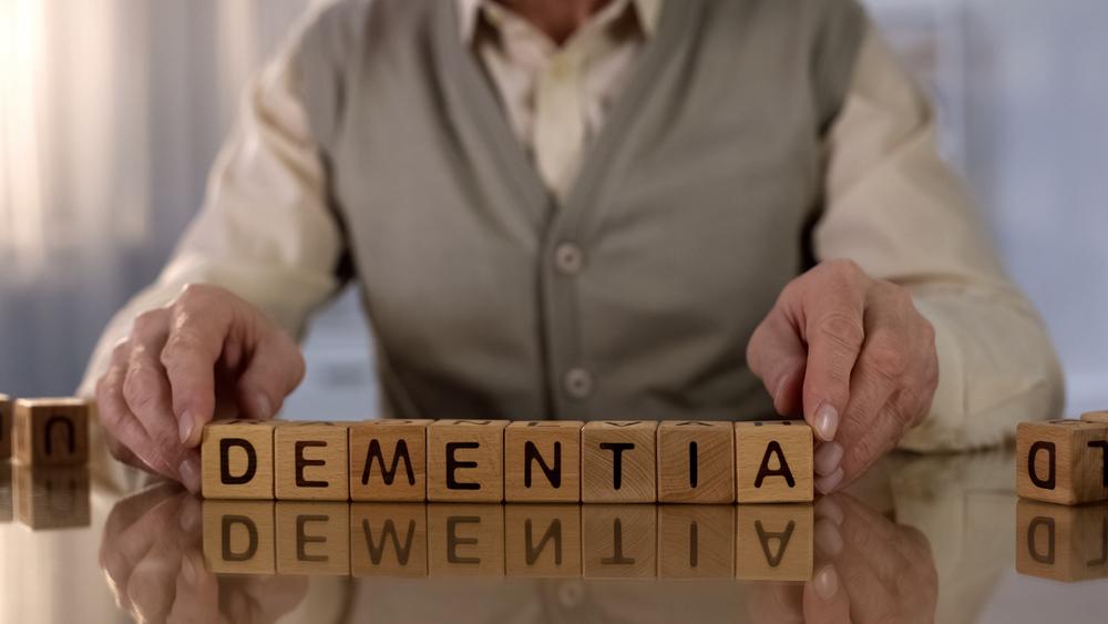 Man holding wooden blocks that read dementia