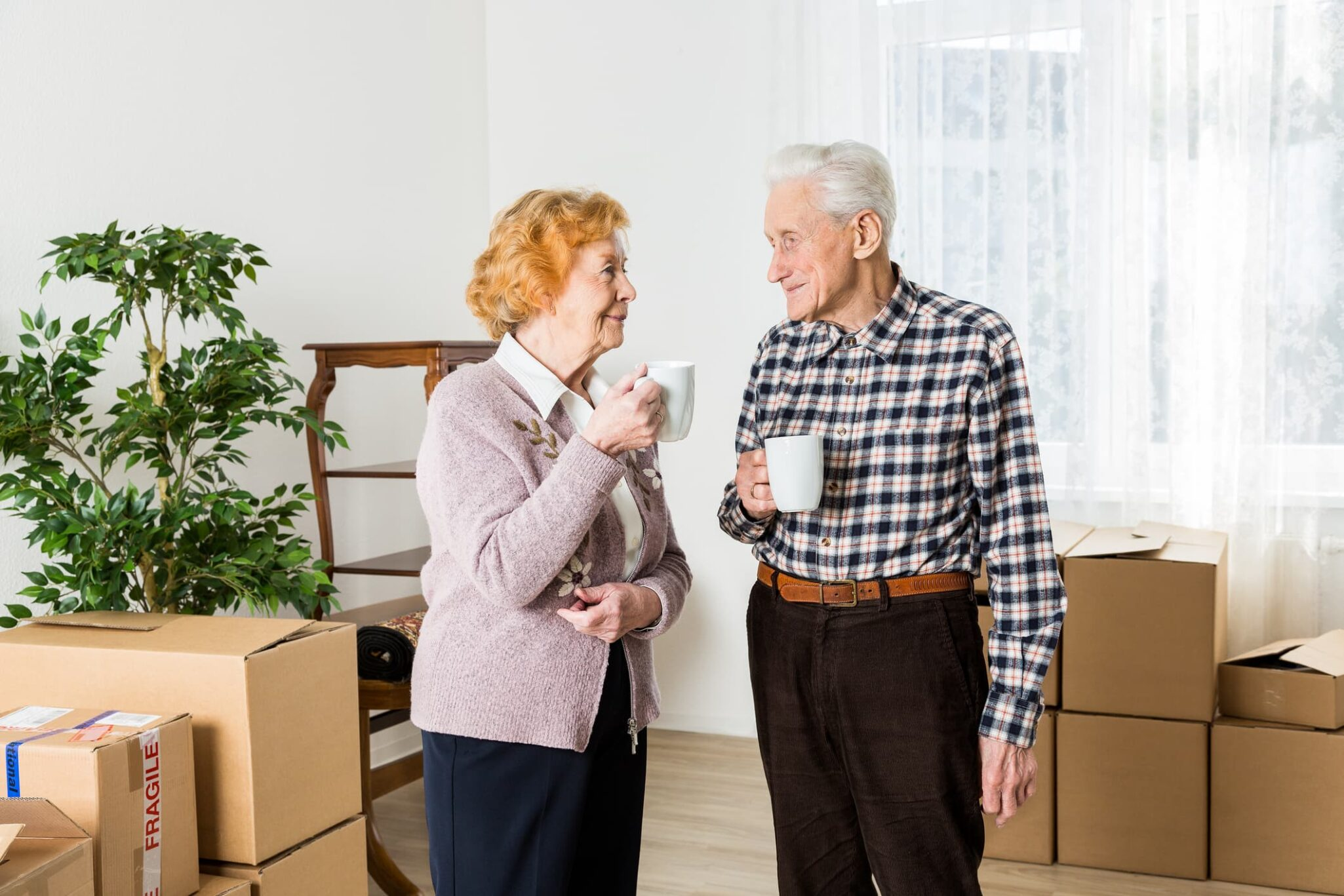 Senior couple enjoying coffee in a room with moving boxes.